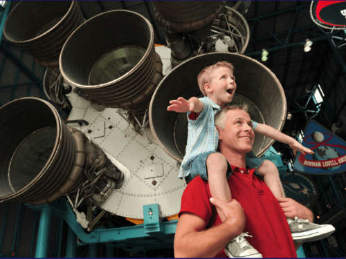 father and son in front of rocket